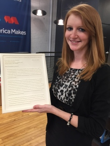 Ashley Martof holds the letter that she designed and printed for President Obama.